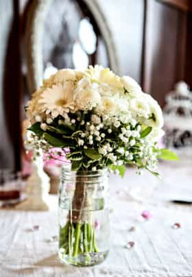 boquet  of White flowers in a mason jar on the table