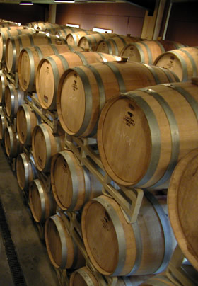 a ton of wine barrels stacked 3 high and two different rows
