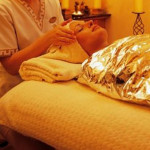 A woman wrapped in a foil cloth laying on her back with her head wrapped in a towel getting her head massage