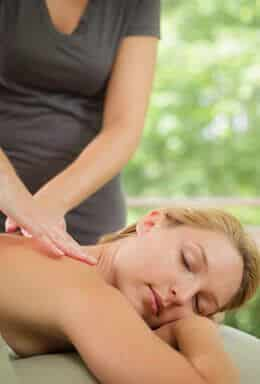 Blonde woman laying on her stomach getting a back massage