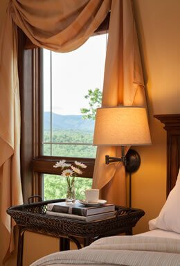 side of the bed with a tan bedspread, nightstand with tow books and a cup of tea, window with a stunning view of the mountains