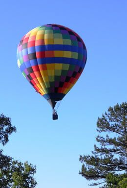 Multi color square boxes on a Hot Air Balloon in the blue sky, in between two trees on the side
