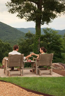 Couple sitting on deck clicking glasses of wine in brown compressed wood and a view of the mountains