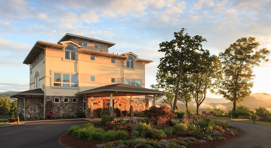 Wide angle of the front of the inn at dusk with the sun setting light on the front, also garden in the circle of the driveway