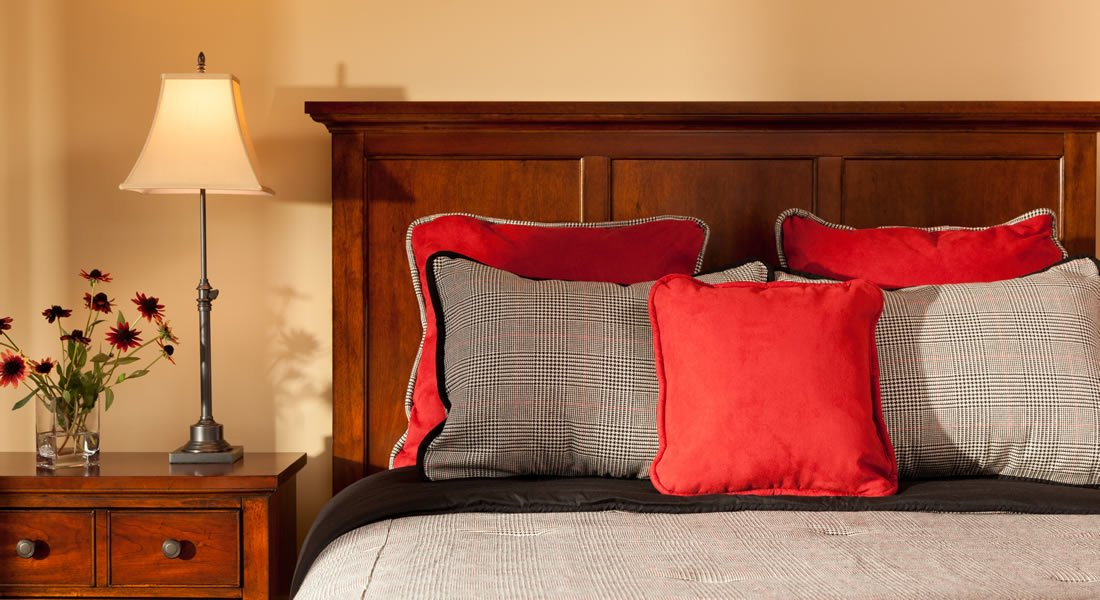Wood headboard with burgundy pillows and stripped black and white