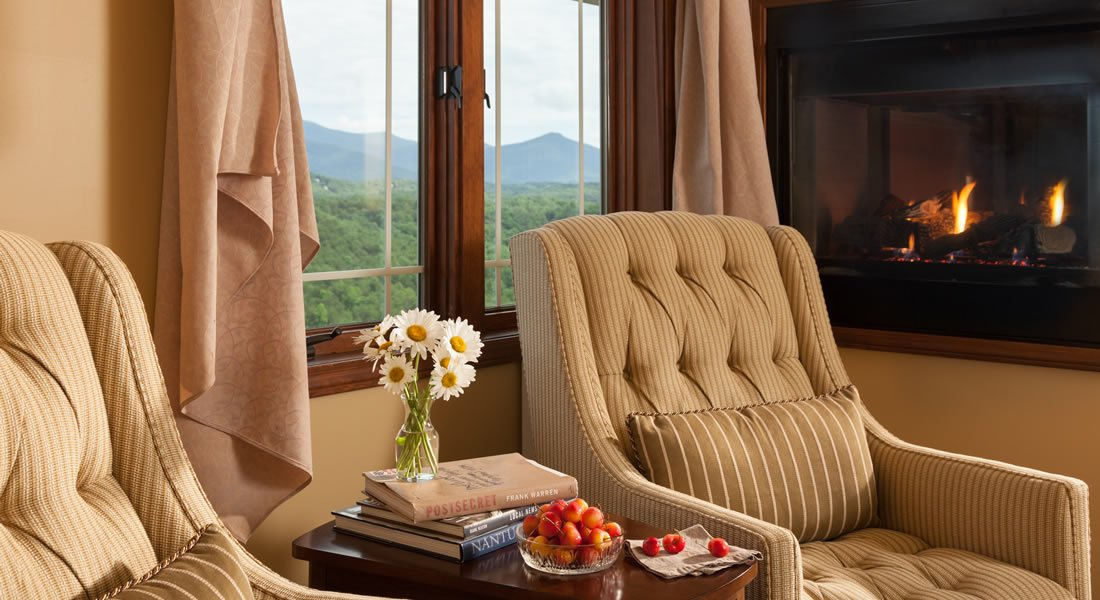 Lite tan chair in the sitting area with a see thru gas fireplace and a window with a view of the mountains
