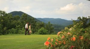 A couple walks along the grounds of Lucille's Mountain Top Inn & Spa. Beautiful green rolling hills are in the background.