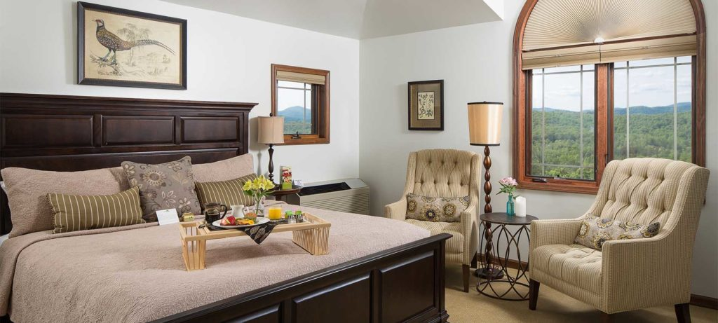 A king sized bed with a tray of food on top, two chairs near the window which overlooks the rolling green mountains.