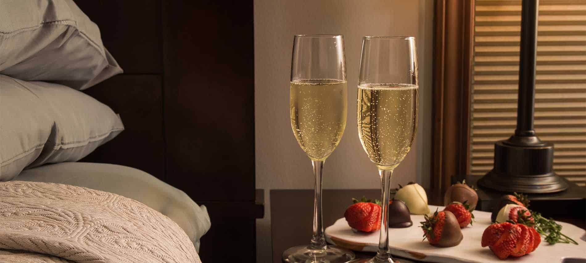 Champagne glasses filled with gently bubbling liquid, next to chocolate covered strawberries on a bedside table.