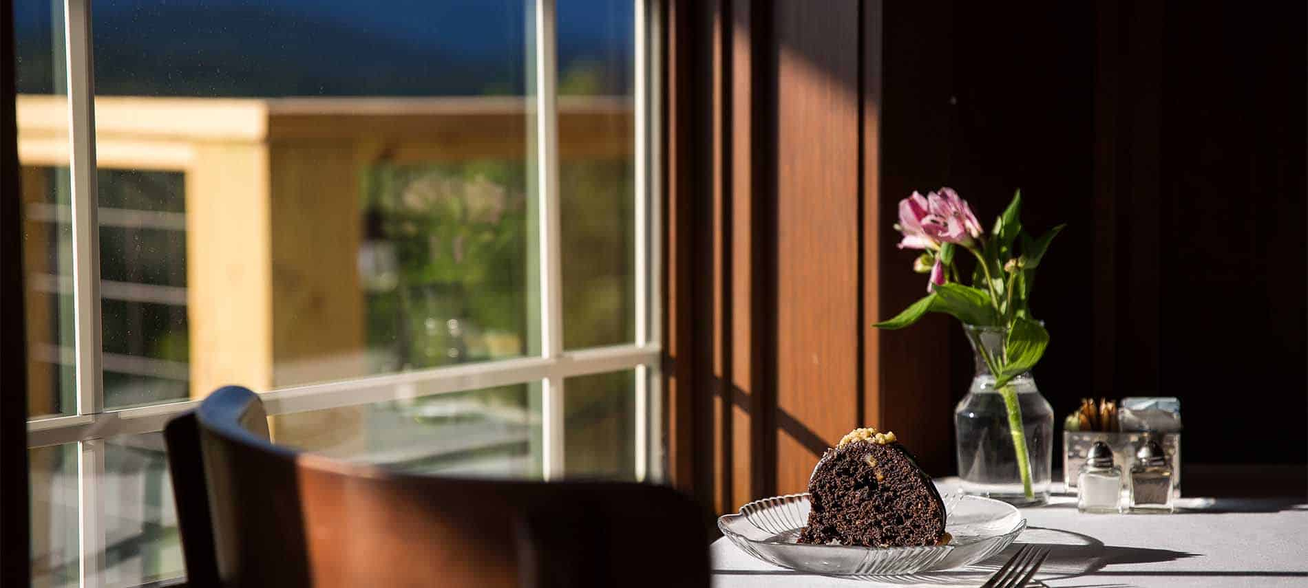 Chocolate cake on a glass plate, on a table with floral centerpiece, in a window with intentional focal blur.