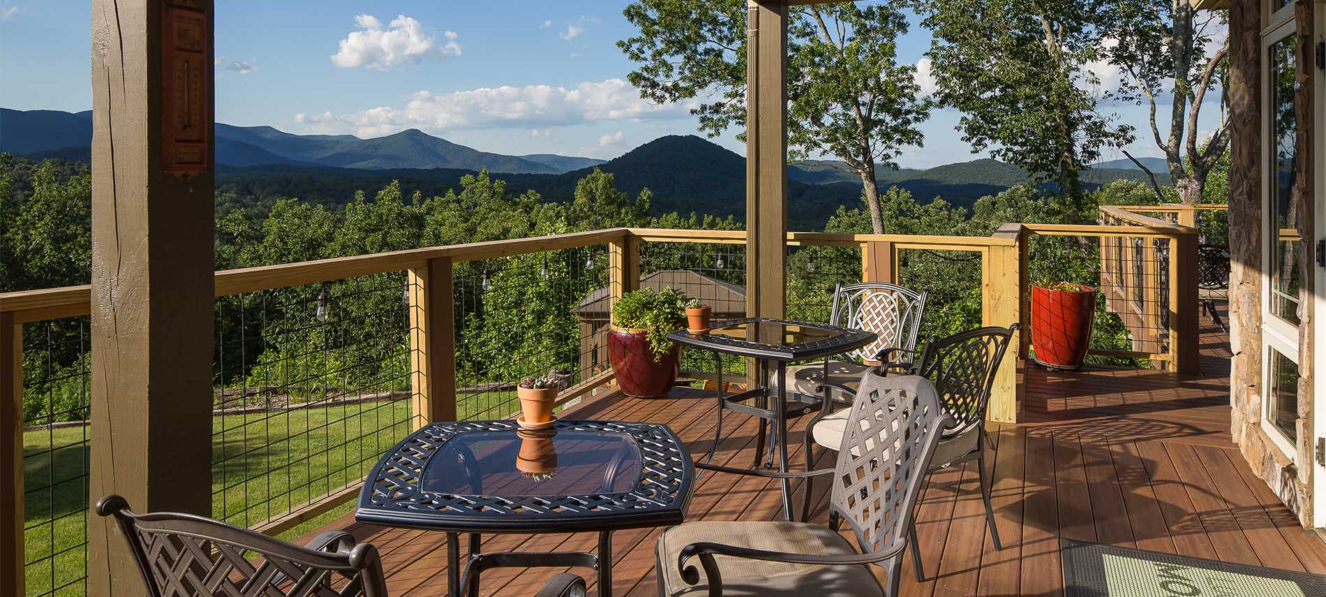 Outdoor patio with reflective dining tables, overlooking a scenic mountain view with sparse clouds dotting the sky.