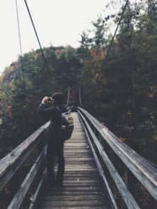 A man standing on the Tallulah Gorge suspension bridge holding a camera