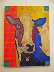 A colorful painting in red/tan/blue of a cow's face.