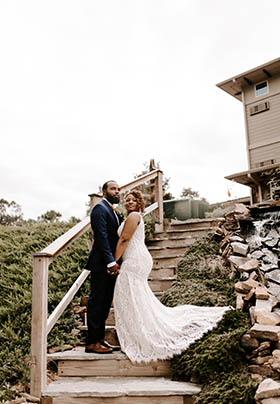 Bride and groom holding hands standing on winding steps with dress train on bushes surrounded by rocks. Tan building at top of steps.