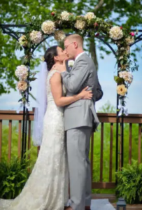 A bride and groom share a kiss on the deck of Lucille's Mountain Top Inn & Spa